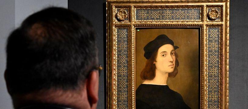 Un homme devant le tableau « Autoportrait » de Raphaël