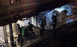 Des pompiers nettoient l'entrée de la station République saccagée pendant un rassemblement de Nuit Debout le 1er mai 2016