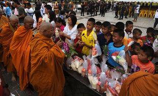 Des moines bouddhistes reçoivent des offrandes à l'occasion de la fête de Asalha Puja à Narathiwat, le 22 juillet 2013.