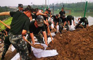 Des militaires renforcent le barrage du réservoir de Wuxing à Xinmie, dans la province du Henan, en Chine, le 22 juillet 2021.