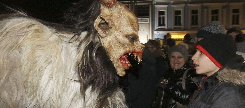 Un Krampus effraie un spectateur lors de la traditionnelle Krampuslauf, une parade où de jeunes hommes prennent l'apparence du démon le temps d'une soirée. A Hollabrunn en Autriche, le 30/11/2019