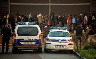 Des policiers surveillent une distribution de nourriture aux migrants sur le port de Calais le 29 octobre 2014