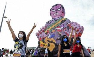 Une jeune femme pose devant une caricature du président brésilien, Jair Bolsonaro à l'occasion d'une manifestation, à Brasilia, réclamant son départ.