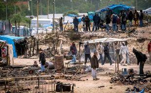 """Des migrants s'activent pour remettre de l'ordre dans la """"Jungle"""" de Calais le 27 mai 2016 au lendemain d'une importante rixe qui a fait 40 blesséz"""