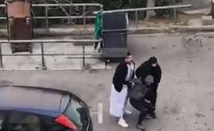 Deux policiers déguisés interpellent un homme.