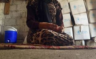 FILE - In this file photo taken Wednesday, Oct. 8, 2014, a 15-year-old Yazidi girl captured by the Islamic State group and forcibly married to a militant in Syria sits on the floor of a one-room house she now shares with her family after escaping in early August, while speaking in an interview with The Associated Press in Maqluba, a hamlet near the Kurdish city of Dahuk, 260 miles (430 kilometers) northwest of Baghdad, Iraq. Hundreds of women have been captured by the group, enslaved and sold, many have been subjected to sexual violence and others have been stoned for adultery. (AP Photo/Dalton Bennett, File)/CAINM501/295523838096/FILE PHOTO TAKEN WEDNESDAY, OCT. 8, 2014. THE GIRL IS NOT IDENTIFIED DUE TO ABUSE AND HER FEAR OF REPRISALS AGAINST HER RELATIVES STILL BEING HELD BY ISLAMIC STATE MILITANTS./1412230649