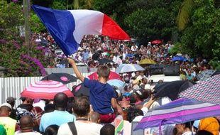 """Un enfant agite un drapeau français le 19 avril 2016 à Mamoutzou pendant la marche contre la violence et l'insécurité dans le département de Mayotte à l'occasion d'une journée """"île morte"""""""