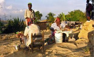 Deux paysannes vendent quelques denrées sur les hauteurs de leur village.
