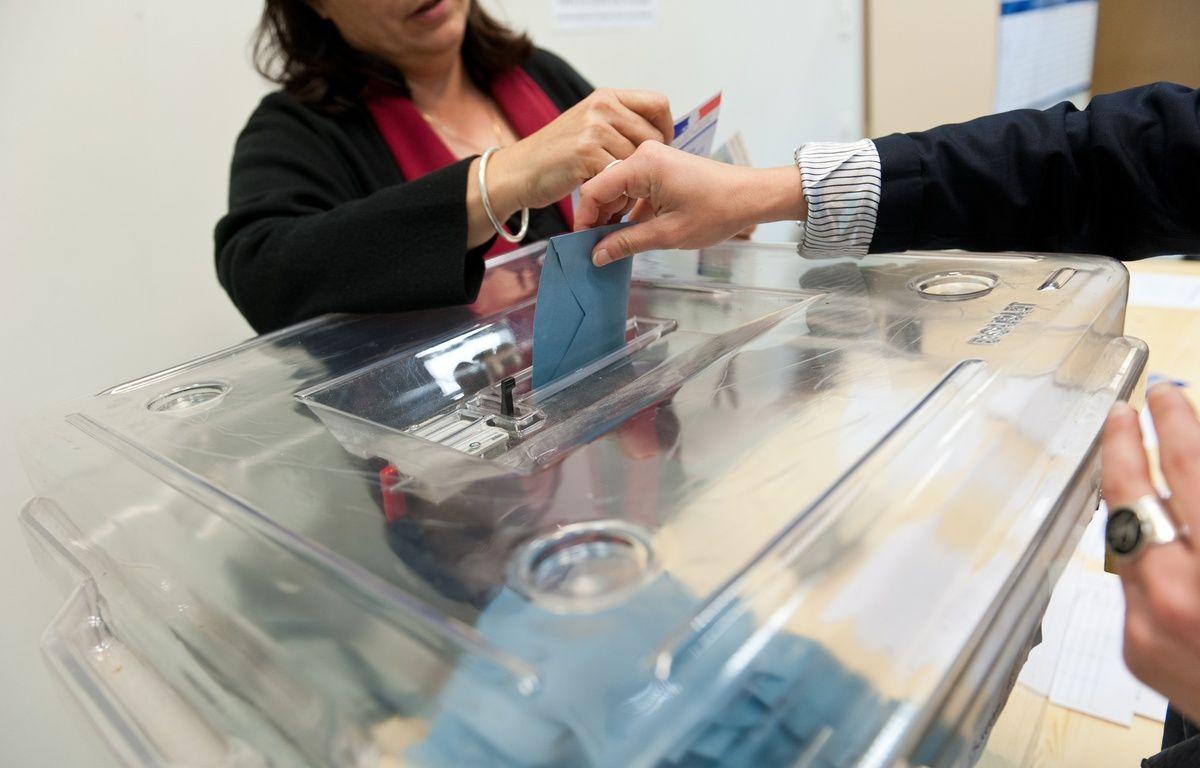 Bordeaux, 22 avril 2012. - Urne de vote et carte d'electeur avec electeur votant. - Photo : Sebastien Ortola – SEBASTIEN ORTOLA