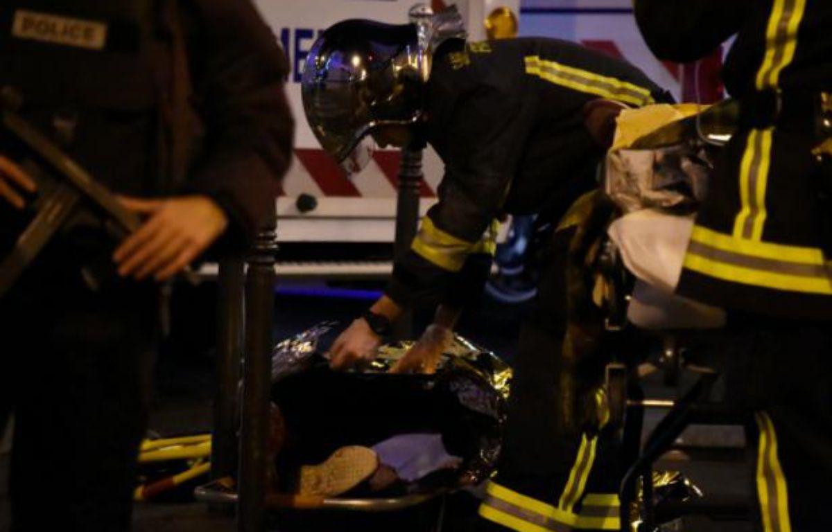 Un pompier vient en aide à une personne blessée le 14 novembre 2015 lors de la prise d'otages au Bataclan, à Paris – DOMINIQUE FAGET AFP
