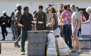 Des migrants reçoivent une aide alimentaire d'une ONG, à Calais.