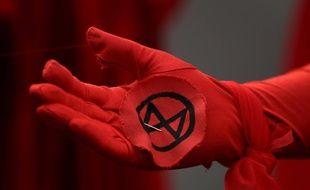 Le logo d'Extinction Rebellion sur le gant d'un membre du mouvement, en octobre 2019