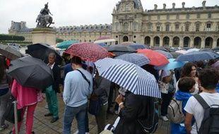 Des visiteurs font la queue sous la pluie devant le musée du Louvre à Paris le 8 août 2014