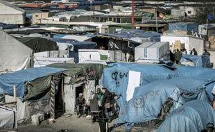 Des migrants discutent à l'extérieur de leurs tentes dans la Jungle de Calais, le 30 mars 2016