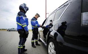 Un gendarme vérifie les papiers d'un conducteur le 1er juin 2014 au Pellerin, près de Nantes.