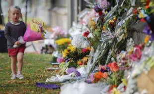 Une petite fille dépose des fleurs sur un mur du jardin botanique de Christchurch, en Nouvelle-Zélande, le dimanche 17 mars 2019, en hommage aux victimes de l'attentat de la mosquée.