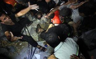 Des secouristes tentent d'extraire des décombres de sa maison un Palestinien blessé le 19 août 2014 à Gaza