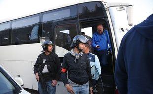 Arme aux poings, des policiers protègent le bus des joueurs Havrais.