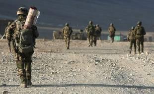 Un soldat français du 13e bataillon de chasseurs alpins en patrouille transporte un tapis afghan, Tagab, Afghanistan, le 7 janvier 2010.