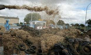 Des agriculteurs déversent de la paille devant un abattoir lors d'une manifestation contre la faiblesse des prix, à Villers-Bocage, le 19 juillet 2015