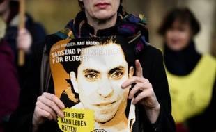 Un militant d'Amnesty Internation tient le 29 janvier 2015 un portrait du blogueur saoudien Raef Badaoui lors d'une manifestation devant l'amabassade d'Arabie saoudite à Berlin.