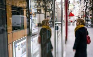 Une femme scrute les annonces de location dans la vitrine d'une agence immobilière, le 18 mars 2013 à Paris