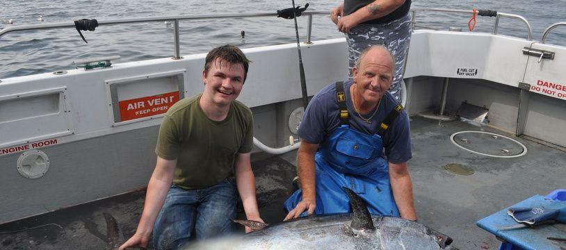 Deux pêcheurs britanniques posent devant un thon rouge pêché au large de la Cornouaille anglaise à l'été 2016.