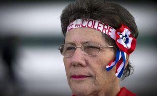 Une femme retraitée manifeste à paris à l'appel de neuf organisations syndicales et associatives pour défendre son pouvoir d'achat, le 30 septembre 2014