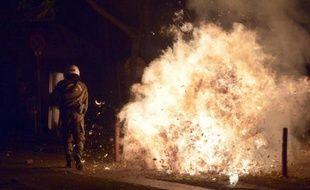 Un coktail molotov explose près d'un policier grec lors d'affrontements avec de jeunes manifestants, le 6 décembre 2014, à Athènes