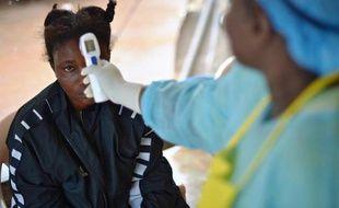 Une jeune fille suspectée d'avoir contracté le virus Ebola se fait prendre la température, le 16 août 2014 à Kenema, au Sierra Leone