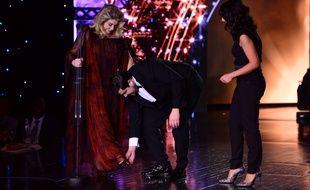 Artus, qui a coprésenté la céremonie avec Estelle Denis (à dr.), est venu au secours de Catherine Deneuve qui avait un talon coincé dans sa robe, lors de la 11e édition des Globes de cristal, au Lido, le 30 janvier 2017.