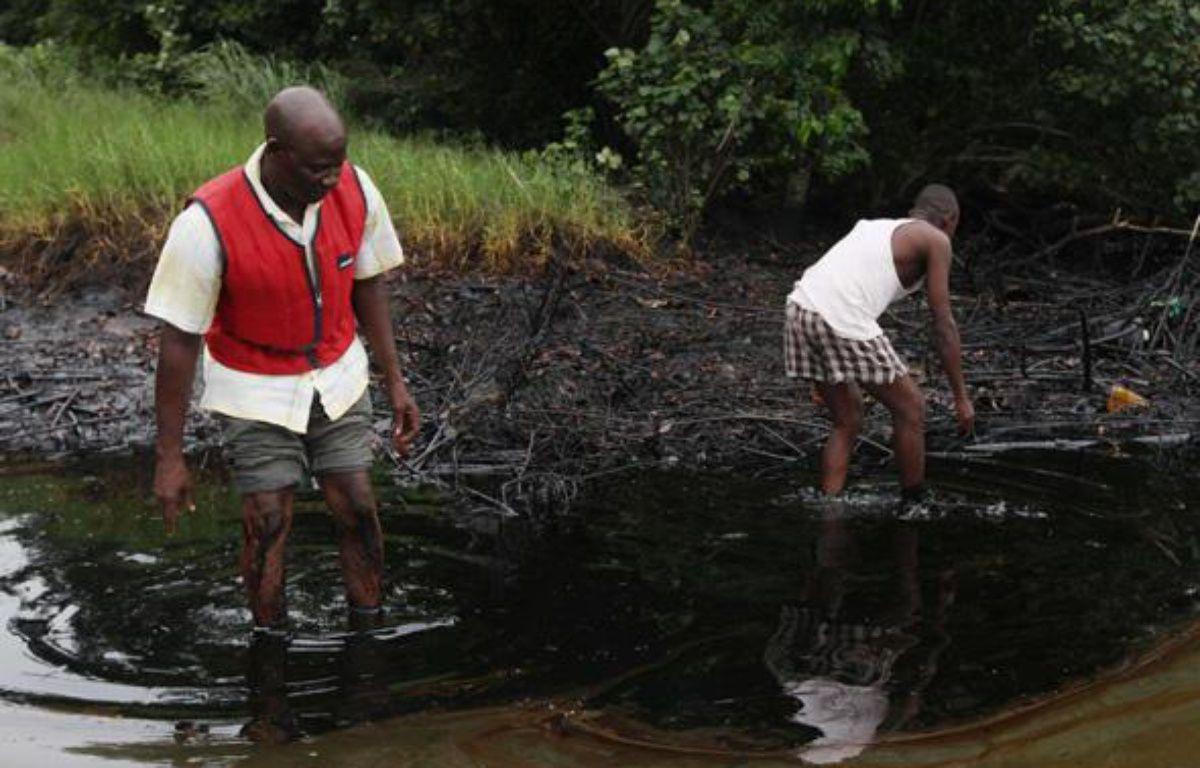 Des hommes marchent dans une nappe de pétrole, dans le delta du Niger, le 20 juin 2010. – Sunday Alamba/AP/SIPA