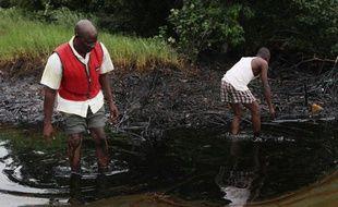 Des hommes marchent dans une nappe de pétrole, dans le delta du Niger, le 20 juin 2010.