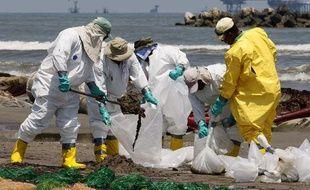 Des équipes de nettoyage s'affairent, le 24 mai 2010, pour effacer les traces de la marée noire sur la plage de Port Fourchon, en Louisiane.