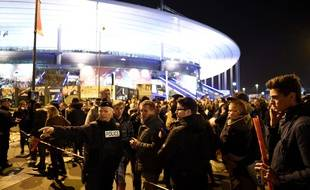Football fans talk to a policeman securing an area outside the Stade de France stadium following the friendly football match between France and Germany in Saint-Denis, north of Paris, on November 13, 2015, after a series of gun attacks occurred across Paris as well as explosions outside the national stadium where France was hosting Germany. At least 18 people were killed, with at least 15 people killed at the Bataclan concert hall in central Paris, only around 200 metres from the former offices of Charlie Hebdo which were attacked by jihadists in January. AFP PHOTO / FRANCK FIFE