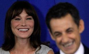 Le président français Nicolas Sarkozy (D) plaisante avec son épouse Carla Bruni-Sarkozy (G) lors d'une conférence à l'ambassade de France à New Delhi, Inde, le 6 décembre 2010.