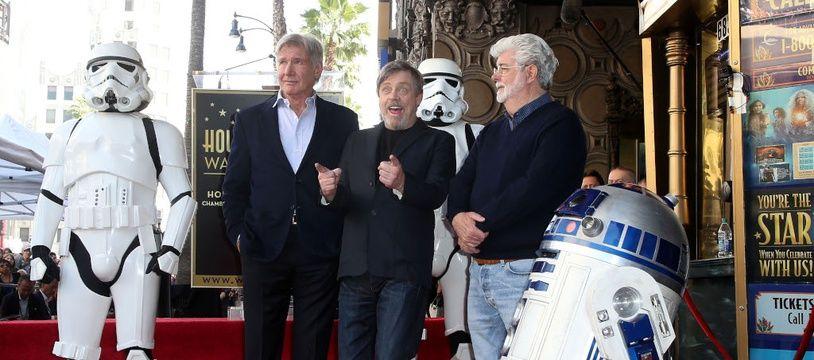Les acteurs Harrison Ford et Mark Hamill, et le réalisateur George Lucas, entourés d'un Stormtrooper et de R2D2
