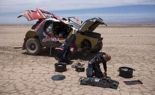 Stéphane Peterhansel et son copilote Jean-Paul Cottret (premier plan) en train de réparer leur Peugeot lors de la 9e étape du Dakar entre Iquique et Calama, le 13 janvier 2015.