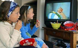 Deux petites filles regardent la télévision en mangeant des sucreries, le 8 octobre 2003 à Rennes.