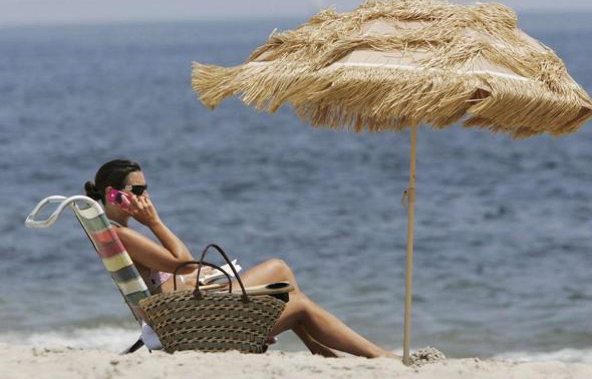 Vacancière qui téléphone sur la plage.  – M. Evans/AP/SIPA