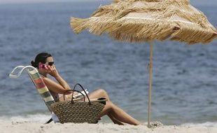 Vacancière qui téléphone sur la plage.