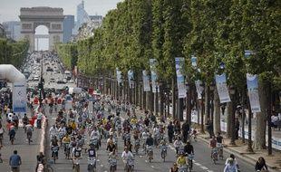 Paris le 16 juin 2013. Avenue des Champs Elysees. Seconde edition des 24h du Velib. Velo. Foule. Arc de triomphe. Forces de l'ordre. Police.