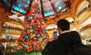 Un homme prend en photo une décoration de Noël dans un centre commercial à Paris.