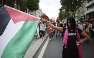 Une manifestante portant le drapeau palestinien durant la manifestation pro-Gaza à Paris qui a réunit plusieurs milliards de personnes samedi 9 aout 2014