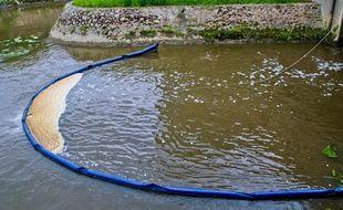 Un barrage flottant pour contenir la pollution sur une rivière. Illustration.