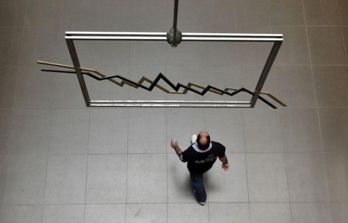 Un homme passe sous un mobil le 2 juin 2011 à la Bourse d'Athènes – AFP PHOTO / Louisa Gouliamaki