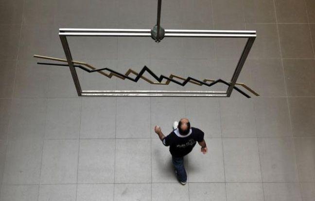 Un homme passe sous un mobil le 2 juin 2011 à la Bourse d'Athènes