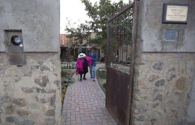 Julia Flores Colque descend l'allée de sa maison accompagnée de son arrière-petite-nièce, Rosa Lucas.