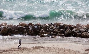 Une personne se promène sur une plage.