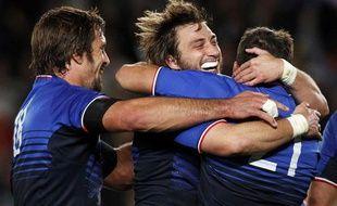 Julien Pierre et Maxime Médard enlacent François Trinh-Duc après la victoire face à l'Angleterre, le 8 octobre 2011